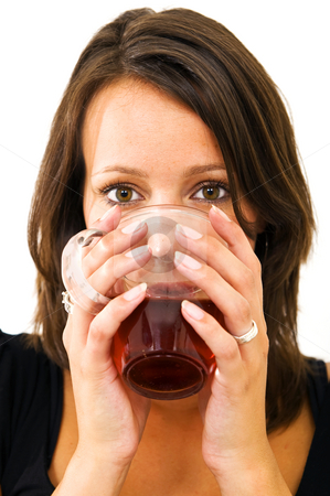 Drinking tea stock photo, Young woman drinking tea from a glass, holding it comfortably with two hands by Corepics VOF