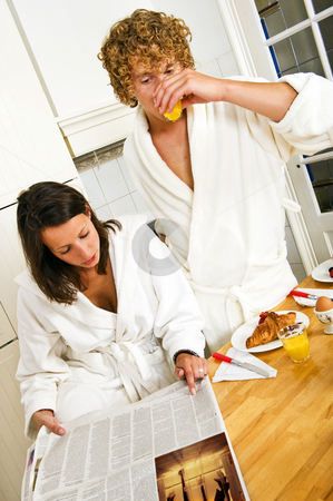 Reading the paper stock photo, Young couple reading the paper on a casual morning breakfast in the kitchen by Corepics VOF