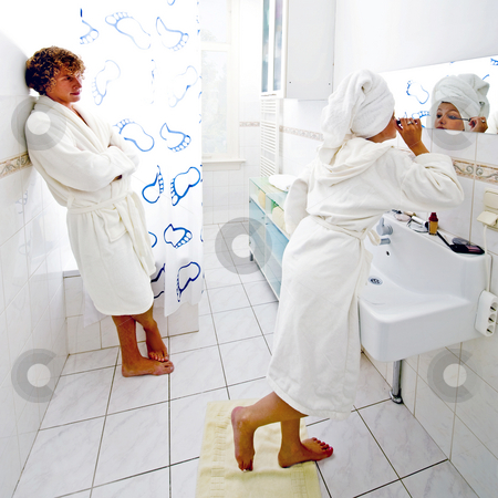 Bathroom queue stock photo, The morning rituals of a couple sharing the same bathroom. A man waiting impatiently for his girlfriend to finish putting up her make-up by Corepics VOF