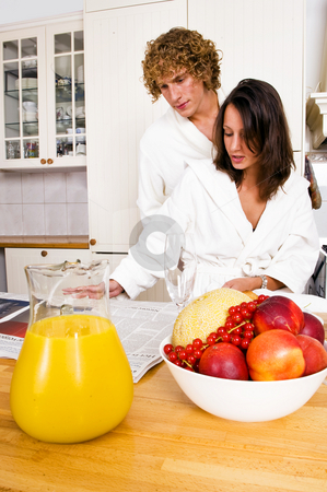 Breakfast stock photo, Young couple reading the paper whilst enjoying a healty breakfast, dressed in bathrobes by Corepics VOF