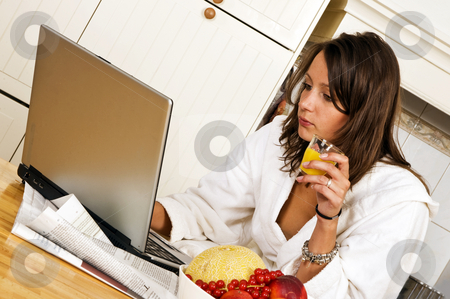 Sunday brunch stock photo, Young woman, catching up with the day's events on her laptop whilst drinking a glass of orange jus, wearing a bathrobe by Corepics VOF