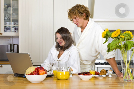 Breakfast stock photo, Young couple wearing bath robes enjoying a healthy breakfast in a kitchen behind a laptop by Corepics VOF
