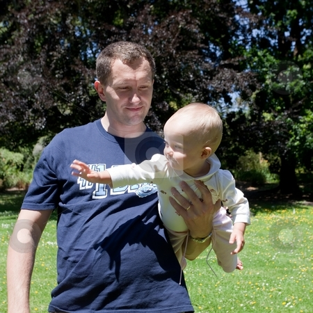 Father's Day stock photo, Father holding his dauther in a park. by Mariusz Jurgielewicz