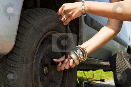 Changing a flat tire stock photo, Woman, loosening the bolts on a wheel to change a flat tire by Corepics VOF