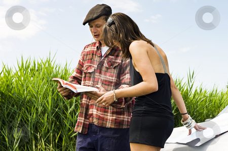 Local guide stock photo, Young woman asking a farmer for information using a guide book and leaning on a map on the hood of her car by Corepics VOF