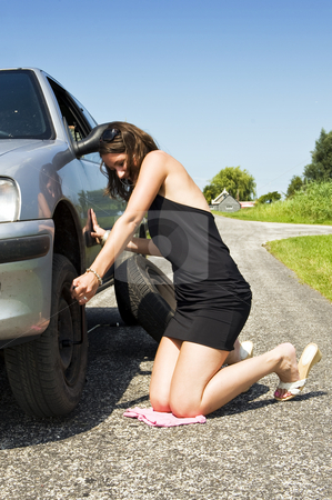 Tightening wheel nuts stock photo, Young woman tightening the wheel nuts on a small rural road by Corepics VOF