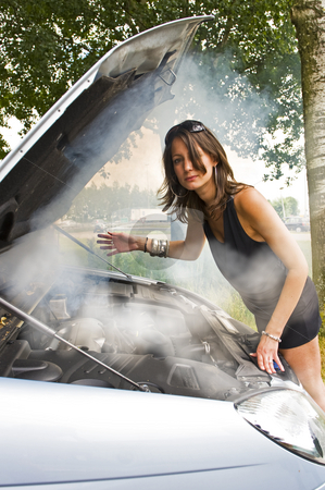 Blown engine stock photo, Young woman waiving through the thick smoke coming from the blown engine of her car, looking at the camera by Corepics VOF