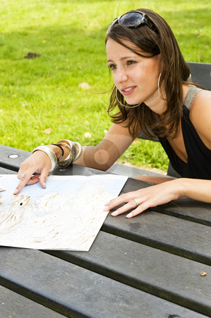 Young woman and road map stock photo, Young woman sitting at a picnic table, pointing at a road map and looking at her travel companion by Corepics VOF