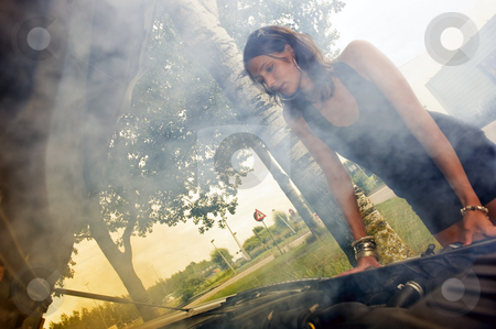 Woman looking at blown engine stock photo, Pretty woman looking sad at the smoke coming from the blown engine of her car by Corepics VOF
