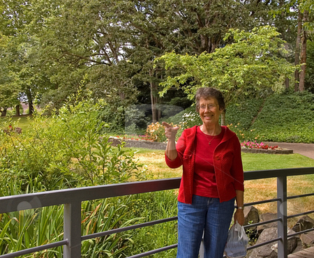 Elderly Woman Pointing Finger With Smile stock photo, This elderly woman is outdoors in a park on a bridge and pointing her finger with a smile on her face in a captivating look. by Valerie Garner