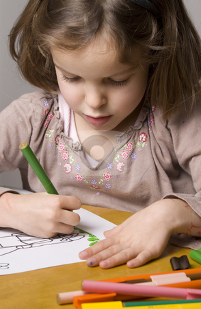 Little girl drawing stock photo, Little girl drawing a picture with coloured pens by Jandrie Lombard