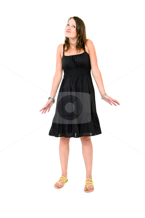 Woman - Playing clueless stock photo, Full body portrait of a young brunette woman in a black summer dress, acting innocent and clueless by Corepics VOF