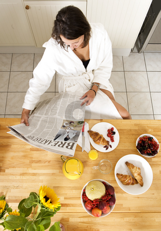 Breakfast stock photo, Pretty young woman reading the mornng paper and enjoying a healthy breakfast with fresh fruit, orange juice and a croissant, dressed in a bathrobe by Corepics VOF
