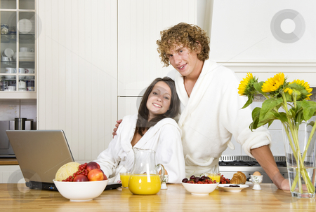 Breakfast together stock photo, Young couple at breakfast, wearing bathrobes in a kitchen and looking at the camera by Corepics VOF
