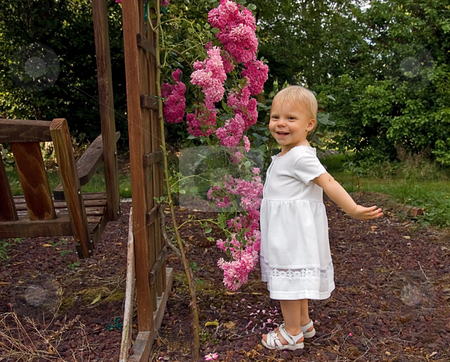 Little Girl in White Dress With Roses stock photo, This little toddler girl is wearing a long white dress and sandals while playing with some pink climbing roses on swing. by Valerie Garner
