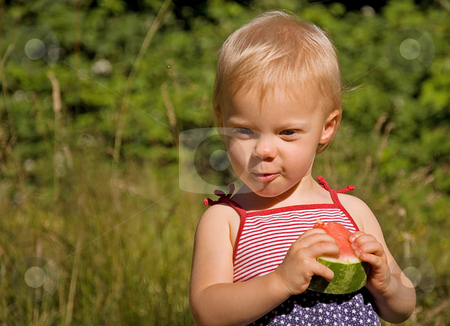 Toddler Girl Eating Watermelon stock photo, This cute Caucasian toddler girl is eating a watermelon wearing a 4th of July themed dress. by Valerie Garner