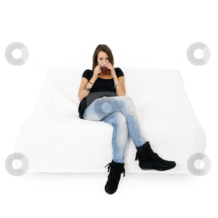 Woman on white couch stock photo, Young woman on a white couch drinking a cup of tea by Corepics VOF