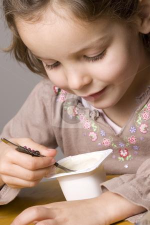 Girl eating yogurt stock photo, Little girl eating yogurt by Jandrie Lombard