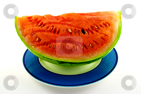 Watermelon stock photo, Slice of watermelon with green skin and red melon with seeds on a blue plate with a white background by Keith Wilson