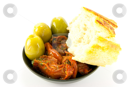 Sun Dried Tomatoes, Olives and Crusty Bread stock photo, Pile of red sun dried tomatoes with three green olives and crusty bread in a small black dish on a white background by Keith Wilson