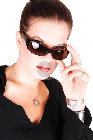 Young woman with sunglasses. stock photo, Young light red haired woman in an black dress standing in the studio  for white background, has her sunglasses in her mouth. by Horst Petzold