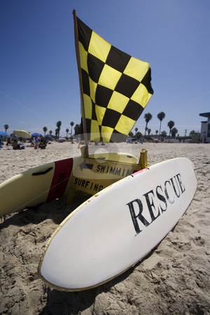 Rescue Surfboard Station stock photo, Rescue surfboard and warning flag on beach by Scott Griessel