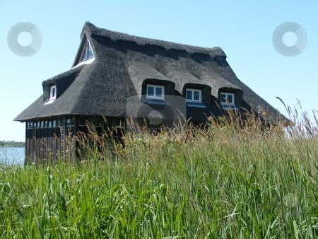 Thatched Hde stock photo, Thatched hide next to a stretch of the broads. by Stuart Atton