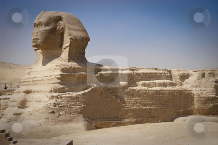 The Sphinx stock photo, The Great Sphinx of Giza is a statue of a reclining lion with a human head that stands on the Giza Plateau on the west bank of the Nile, near modern-day Cairo, in Egypt. It is the largest monolith statue in the world, standing 73.5 m (241 ft) long, 6 m (20 ft) wide, and 20 m (65 ft) high. It is the oldest known monumental sculpture, built on the third millennium BC.The Great Sphinx was thus believed according to Mythology to stand as guardian of the tombs on the Giza Plateau, facing out from the world of the dead towards the rising sun. by Amr Hassanein