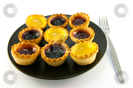 Jam Tarts stock photo, Selection red and yellow small jam tarts on a black plate with a fork on a white background by Keith Wilson