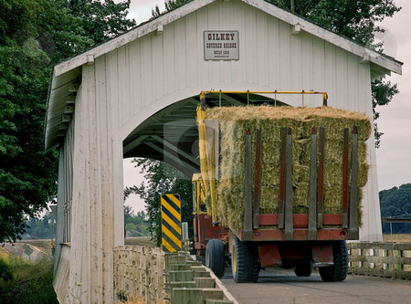 Big Hay Truck Crossing Covered Bridge stock photo, This large hay truck in a rural area is about to cross a turn of the century white covered bridge. by Valerie Garner