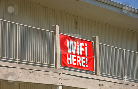 Building With WiFi Here Sign stock photo, This off white building has a red banner sign saying the words WiFi Here. by Valerie Garner