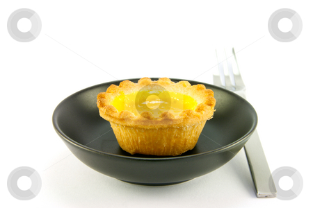 Lemon Jam Tart stock photo, Single small yellow lemon jam tart in a small black dish with a fork on a white background by Keith Wilson