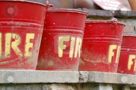 Fire buckets stock photo, A row of red fire buckets. by Jeff Carson