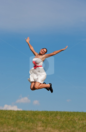 Smiling Jumping Girl stock photo, A beautiful girl in a white dress jumping for joy on a grassy, green hill, on a warm summer day. by Brenda Carson