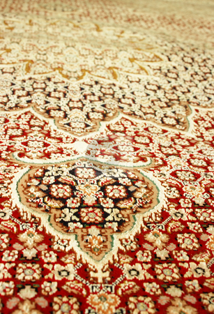 Persian Carpet stock photo, Closeup shot of persian carpet, showing rich red and gold colors. Shallow depth of field by Martin Darley