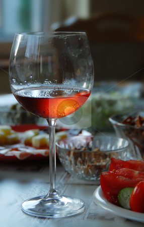 Wineglass with highlighted rose wine stock photo, Wineglass with highlighted rose wine on served table by Julija Sapic