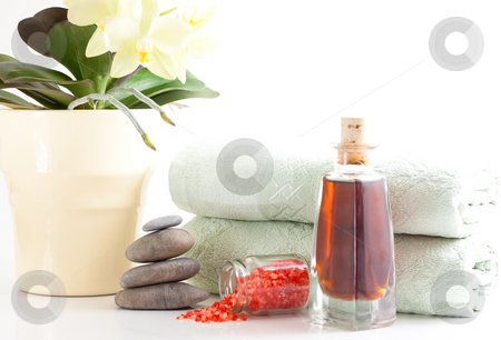 Orchied, massage stones and towels stock photo, Yellow orchid, massage stones, bath salt, massage oil and two towels isolated on white background by Alexander Zschach