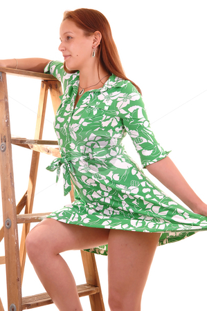 Happy lady on ladder. stock photo, Happy young woman in a green dress standing on an stepladder and lifting up her dress to shoo the nice legs, on white background. by Horst Petzold