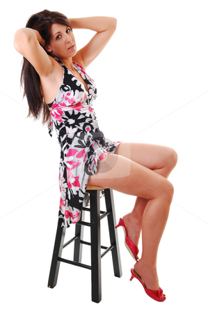 Woman sitting on chair. stock photo, Lovely young woman in high heels sitting on a chair in the studio with long  brown hair, shooing her nice legs. On white background. by Horst Petzold