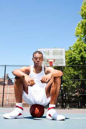 Basketball player sitting on ball stock photo, Handsome sporty African-American male basketball player with attitude dressed in white sitting on his ball outdoor on a summer day in a basketball court. by Paul Hakimata
