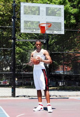 Basketball player with ball stock photo, Handsome sporty African-American male basketball player with attitude dressed in white standing holding his ball with both hands outdoor on a summer day in a basketball court. by Paul Hakimata