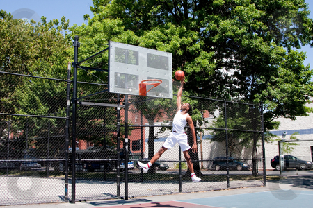 Jumping basketball player stock photo, Sporty handsome African-American man dressed in white jumping in the air reaching for the basket while playing basketball in an outdoor court on a summer day by Paul Hakimata