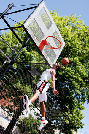 Jumping basketball player stock photo, Sporty handsome African-American man dressed in white jumping in the air reaching for the basket while playing basketball in an outdoor court on a summer day trying to dunk the ball by Paul Hakimata