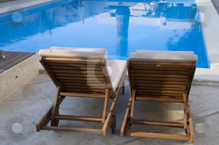 View on the swimming pool stock photo, Two chairs to sit and relax and view at the swimming pool by Chris Willemsen