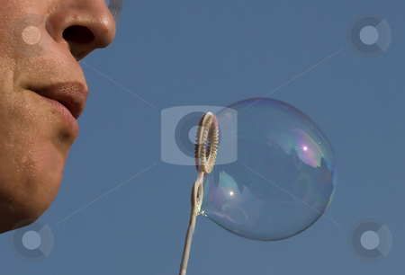 Woman blowing bubbles stock photo, Woman blowing bubbles from water and soap by Chris Willemsen