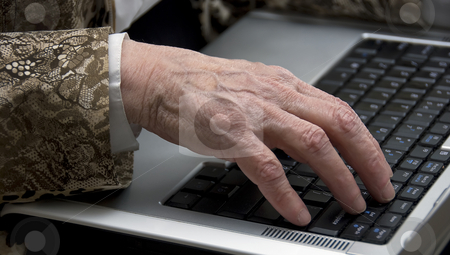 Old womans hand with laptop stock photo, Hand of a woman older then 80 , working on a mobile laptop by Chris Willemsen