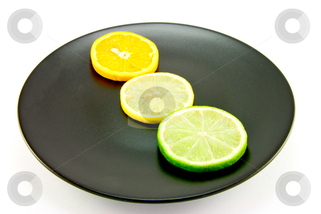 Citrus Slices on a Black Plate stock photo, Lemon, lime and orange slices in a line on a black plate on a white background by Keith Wilson