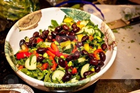 Greek Salad stock photo, Greek salad is essentially a tomato salad made of sliced or chopped tomatoes with a few slices of cucumber, red onion, feta cheese, and kalamata olives, seasoned with salt, black pepper, oregano, and basil and dressed with olive oil. by Mariusz Jurgielewicz