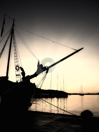 Sepia nautical sunset stock photo, Sepia toned image and silhouette of an old ship in the Adriatic port in the quiet and tranquil  evening. by Sinisa Botas