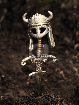 Viking's grave stock photo, Warrior's grave with a sword and helmet instead of the cross.  Sepia toned image. by Sinisa Botas
